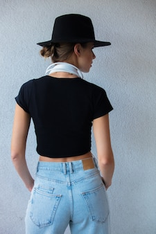 Mulher jovem com chapéu e roupas estilo anos 90 na parede branca
