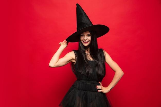 Mulher jovem com chapéu e vestido de bruxa em fundo vermelho
