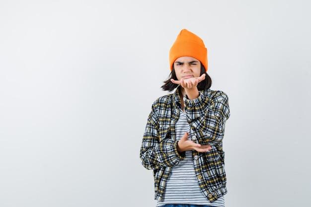 Mulher jovem com chapéu laranja e camisa quadriculada fingindo que segura algo
