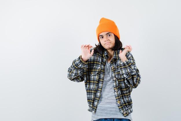 Mulher jovem com chapéu laranja e camisa xadrez em pé, encolhendo os ombros