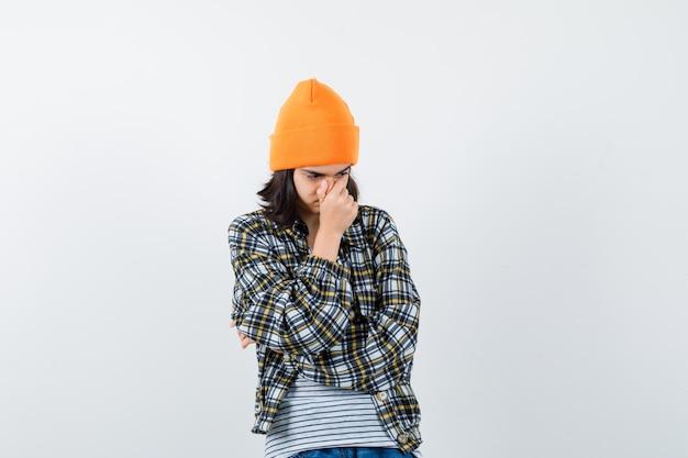 Mulher jovem com chapéu laranja segurando a mão no nariz e parecendo triste