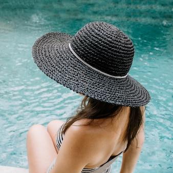 Mulher jovem com chapéu relaxando perto da piscina