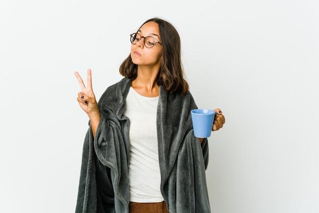 Mulher jovem com cobertor alegre e despreocupada mostrando um símbolo da paz com os dedos