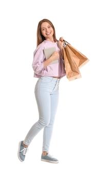 Mulher jovem com computador tablet e sacolas de compras em branco