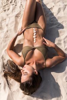 Mulher jovem com conchas na barriga deitada na areia da praia