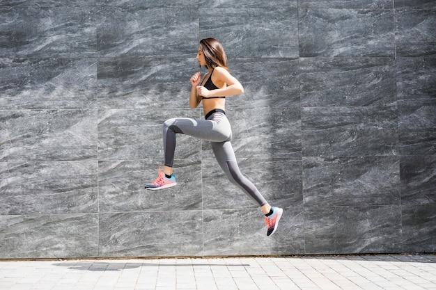 Mulher jovem com corpo apto, pulando e correndo contra uma parede cinza.