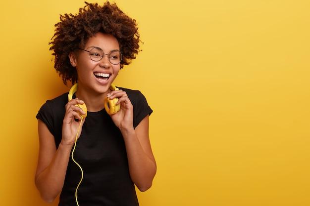 Mulher jovem com corte de cabelo afro com fones de ouvido amarelos