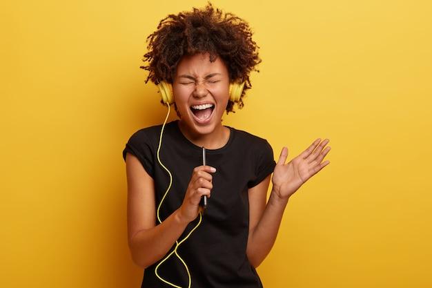 Mulher jovem com corte de cabelo afro e fones de ouvido amarelos