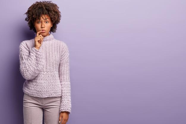 Mulher jovem com corte de cabelo afro e suéter roxo