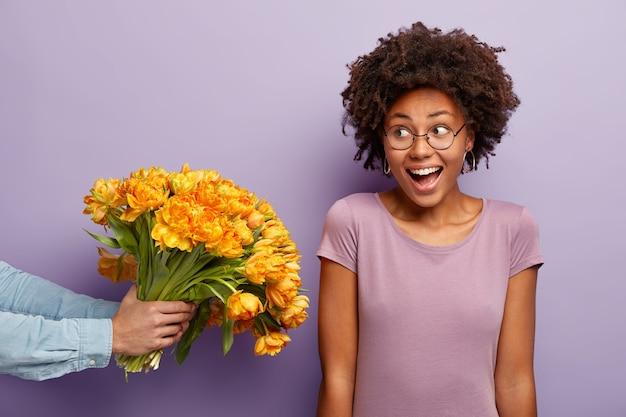 Mulher jovem com corte de cabelo afro recebendo buquê de flores