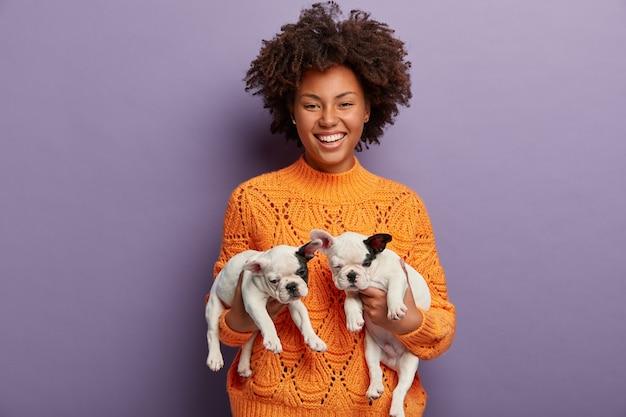Mulher jovem com corte de cabelo afro segurando filhotes