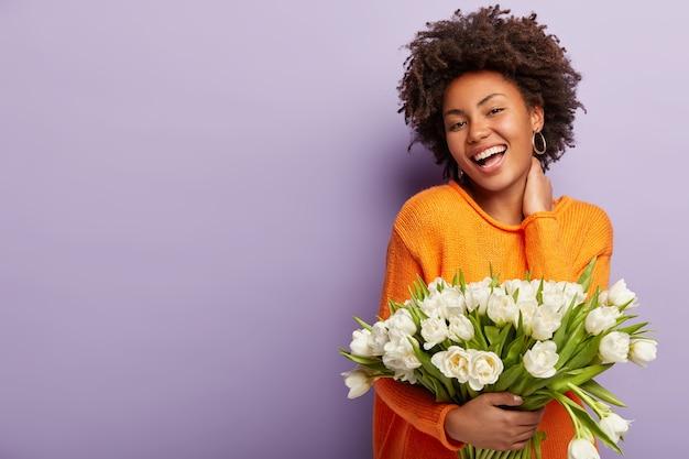 Mulher jovem com corte de cabelo afro segurando um buquê de flores brancas