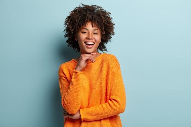Mulher jovem com corte de cabelo afro usando um macacão laranja