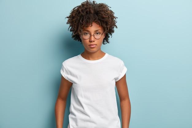 Mulher jovem com corte de cabelo afro vestindo camiseta branca
