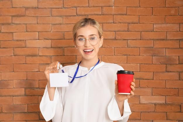 Mulher jovem com crachá em branco e xícara para viagem perto de uma parede de tijolos