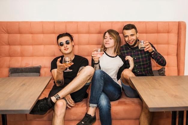 Mulher jovem, com, dela, dois, macho, amigos, bebidas bebendo, em, restaurante