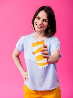 Mulher jovem com dentes sensíveis bebendo água fria na cor de fundo Foto Premium