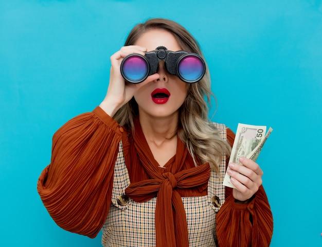 Mulher jovem com dinheiro e binóculo azul