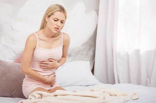Mulher jovem com dor abdominal enquanto está sentada na cama em casa