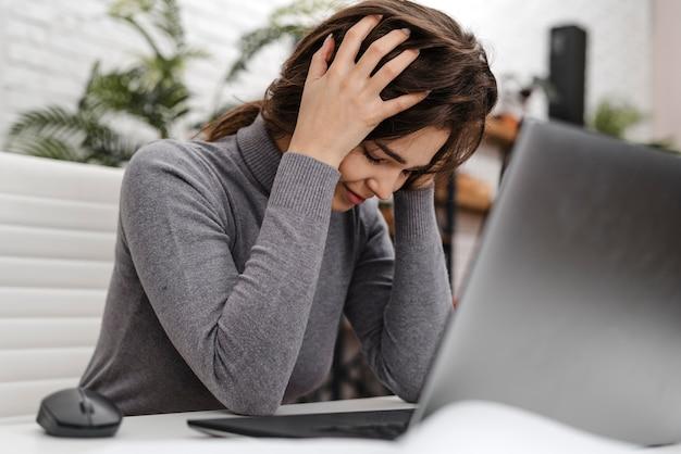 Mulher jovem com dor de cabeça enquanto trabalha em casa