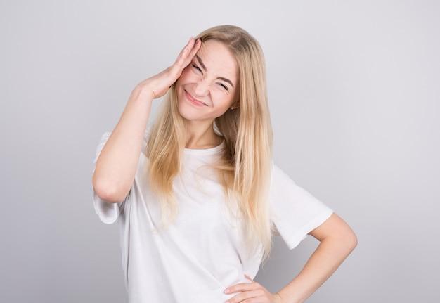 Mulher jovem com dor de cabeça segura as têmporas com as mãos. conceito de saúde, enxaqueca e dor de cabeça.
