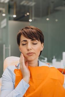Mulher jovem com dor de dente e esperando pelo dentista