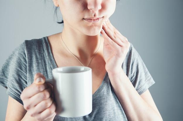 Mulher jovem com dor de dente na pele cinza