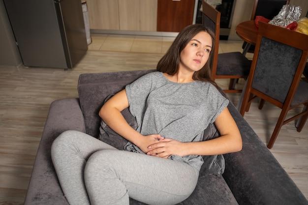 Mulher jovem com dor de estômago, vista de cima