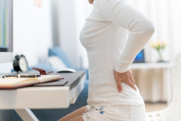 Mulher jovem, com, dor traseira, trabalhando, com, computador, cuidados de saúde, e, conceito médico
