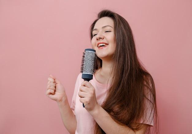 Mulher jovem com escova de cabelo e microfone na mão em fundo rosa
