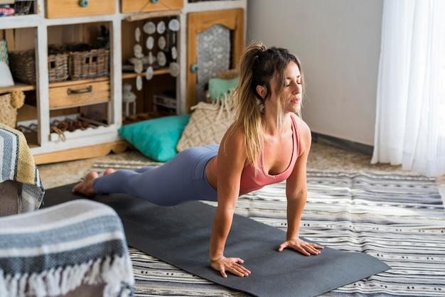 Mulher jovem com estilo de vida ativo fazendo flexões ou exercícios de prancha em casa no chão com esteira de ginástica interna para pessoas do sexo feminino