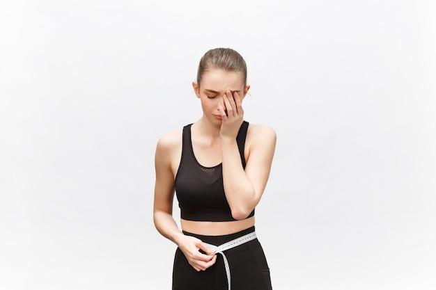 Mulher jovem com excesso de peso em um top esportivo, tristemente olhando o resultado da medição da cintura