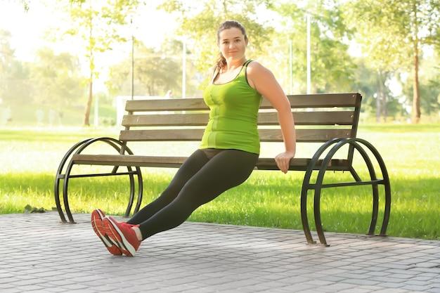 Mulher jovem com excesso de peso, exercitando-se no parque. conceito de perda de peso