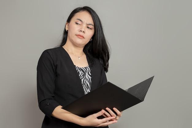 Mulher jovem com expressão facial atônita segurando uma pasta enquanto olha para o lado
