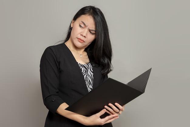 Mulher jovem com expressão facial atônita segurando uma pasta enquanto olha para trás
