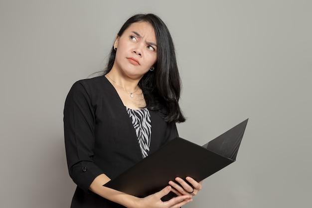 Mulher jovem com expressão facial de espanto enquanto olha para cima e segura a pasta