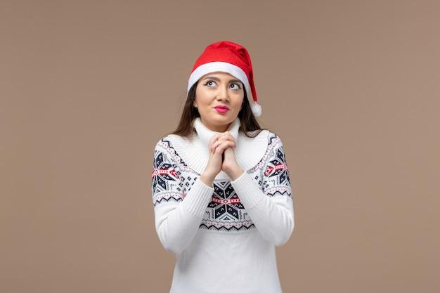 Mulher jovem com expressão sonhadora em um fundo marrom emoção de ano novo de natal