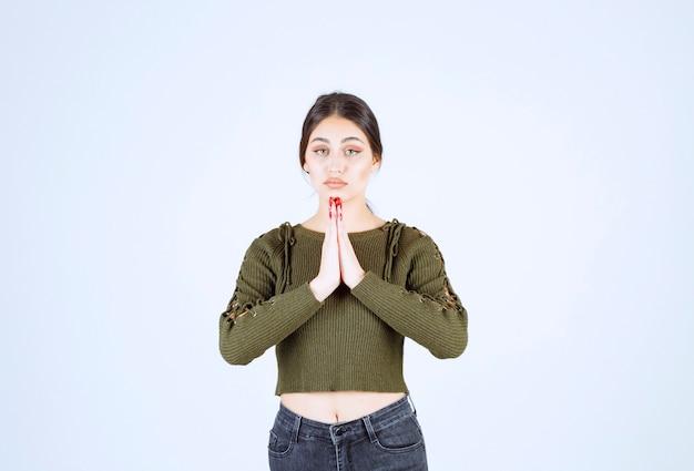 Mulher jovem com expressão triste a rezar na parede branca