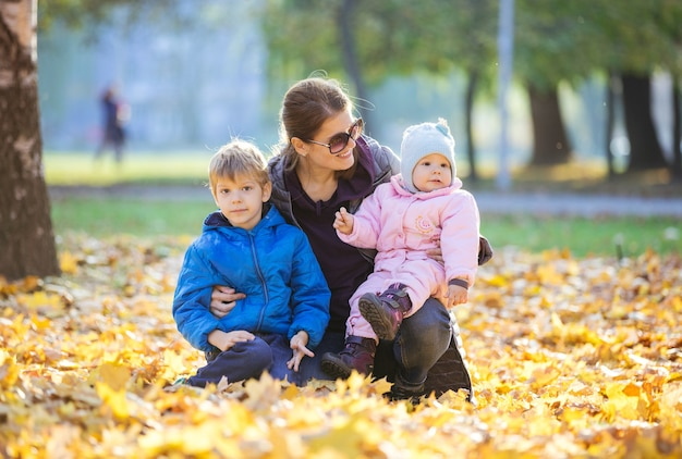 Mulher jovem com filho pré-escolar e filha bebê curtindo um lindo dia no parque de outono