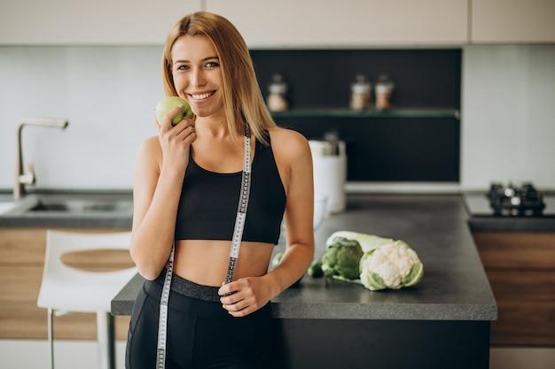 Mulher jovem com fita métrica na cozinha