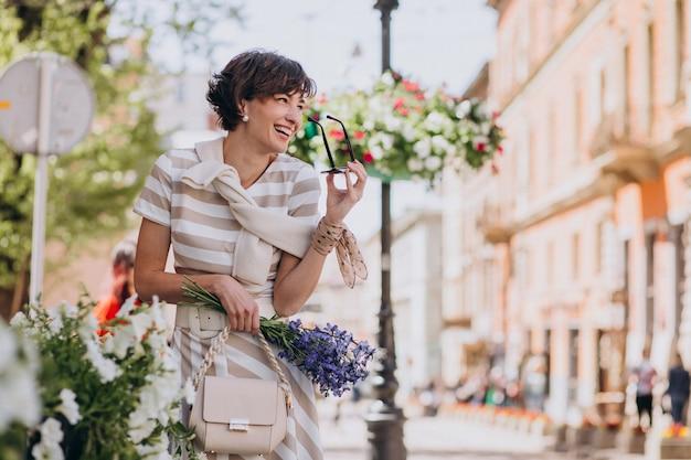 Mulher jovem com flores caminhando pela cidade