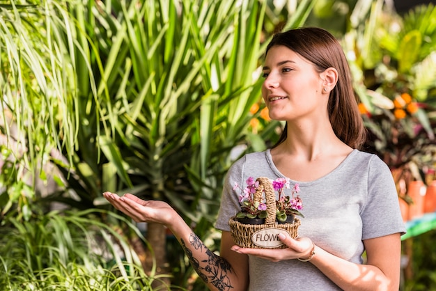 Mulher jovem, com, flores, em, cesta, mostrando, em, plantas verdes