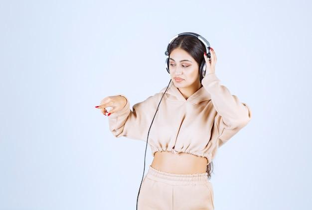 Mulher jovem com fones de ouvido apontando ou notando alguém à esquerda