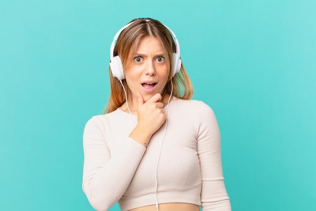 Mulher jovem com fones de ouvido, boca e olhos bem abertos e mão no queixo
