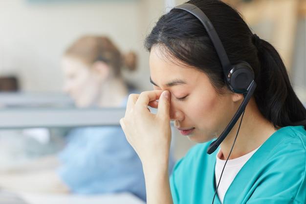 Mulher jovem com fones de ouvido, cansada do trabalho, com dor de cabeça enquanto está sentada à mesa no escritório