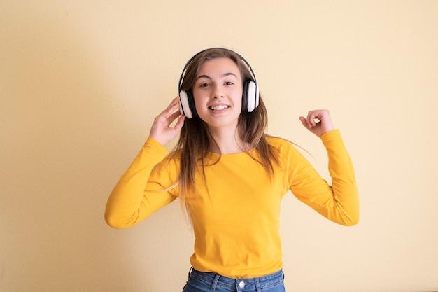 Mulher jovem com fones de ouvido dançando em fundo amarelo