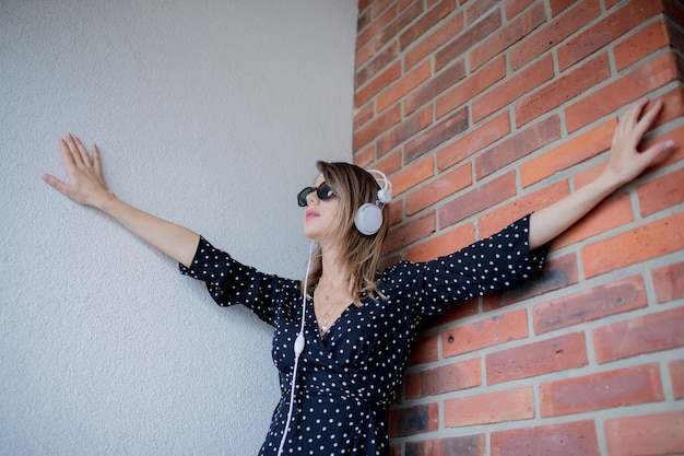 Mulher jovem com fones de ouvido e óculos de sol na parede de tijolos
