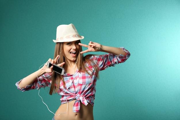 Mulher jovem com fones de ouvido em turquesa