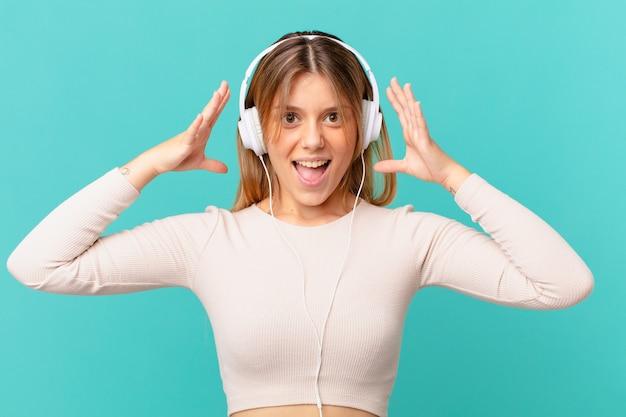 Mulher jovem com fones de ouvido gritando com as mãos para o alto