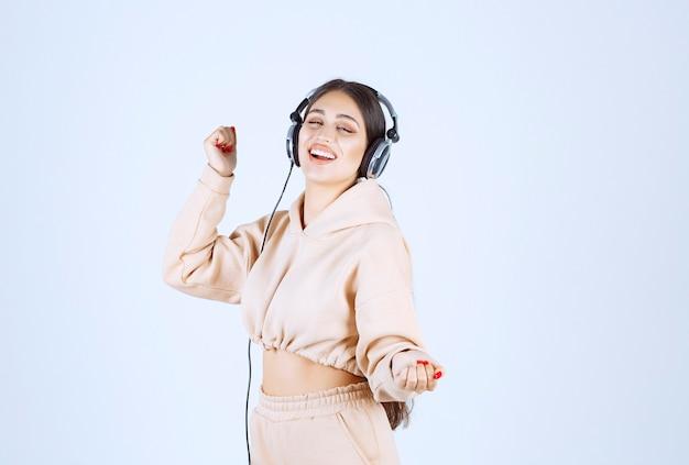 Mulher jovem com fones de ouvido, ouvindo música e dançando